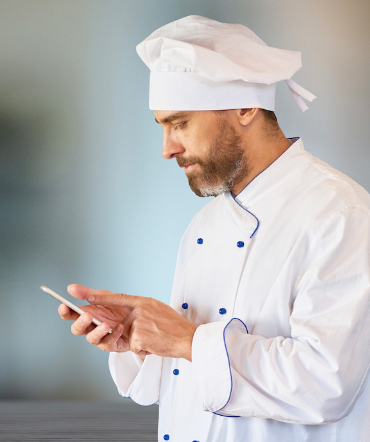 chef looking at phone